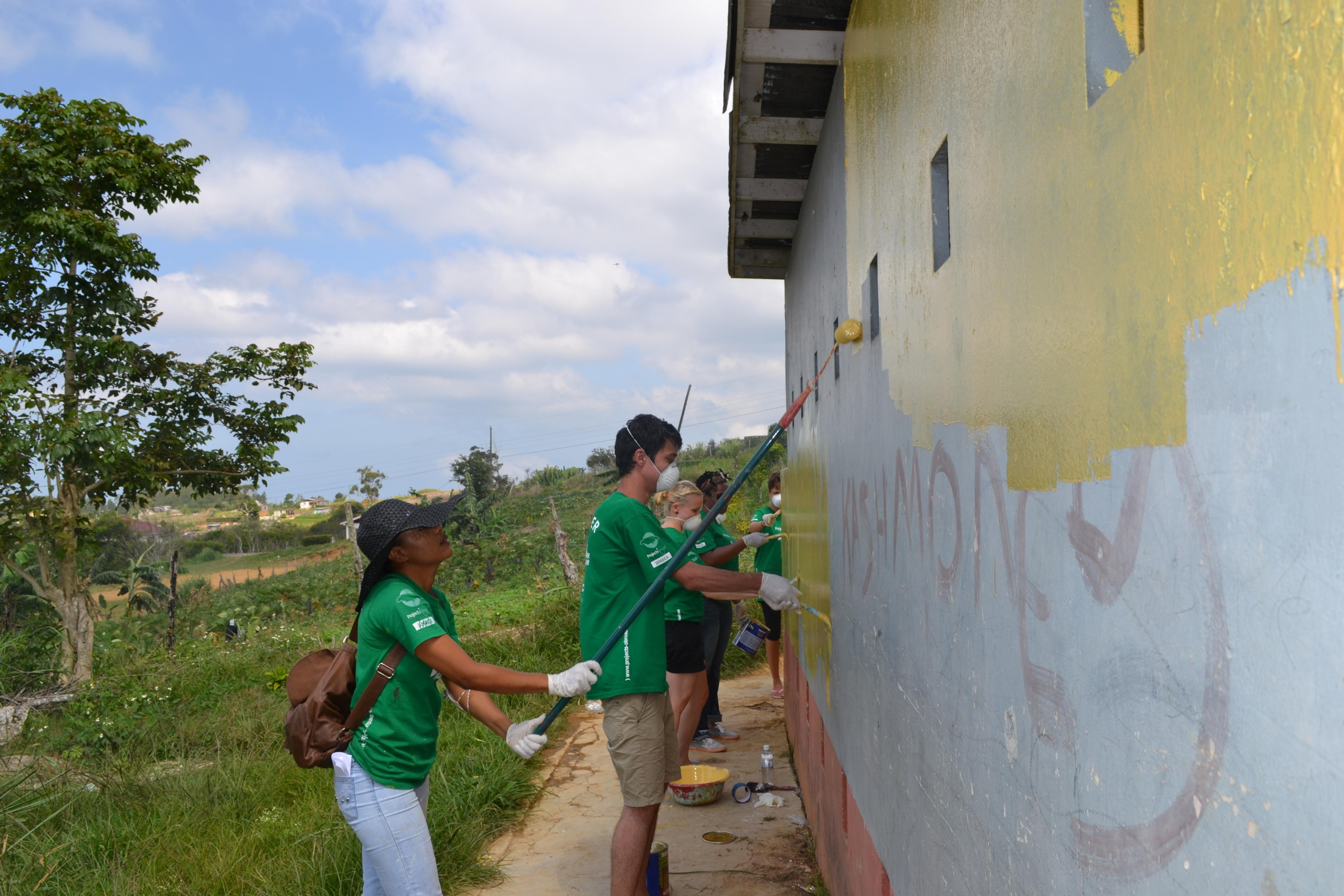 A group of Projects Abroad volunteers help to paint a toilet facility as part of their buidling volunteer work in Jamaica.
